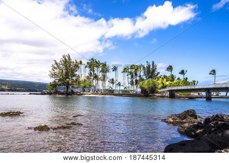 Coconut Island Hawaii depicts a calm day with gentle waves washing ashore highlighting the tropical climate and look of paradise.