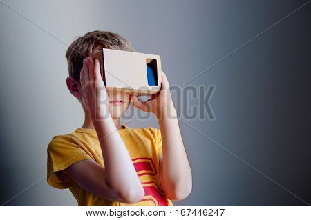 Young boy with hand holding virtual reality device