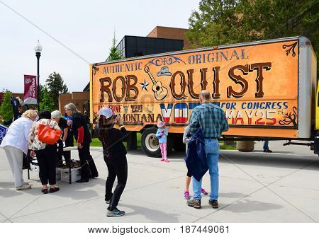 MISSOULA, MONTANA, USA - May 20, 2017: Cowgirl poses for photos in front of US House of Representative candidate Rob Quistâ??s truck for 2017 Montana special election at University of Montana