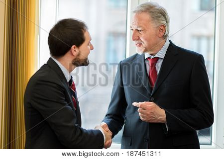 Businesspeople giving handshake in the office