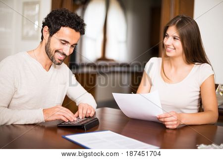 Couple calculating their expenses together. Shallow depth of field, focus on the man