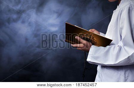 Asian muslim kid reading koran with smoke background