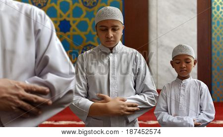 Muslim man and muslim kid praying in mosque