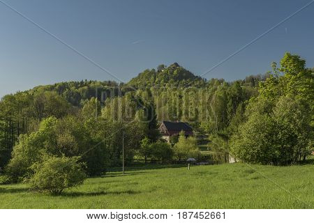 Spring blue sunny day with Tolstejn castle and green meadows