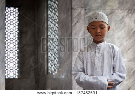 Asian muslim kid praying to god in mosque