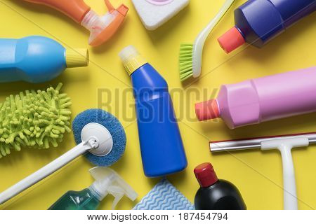 House cleaning product on yellow background, top view