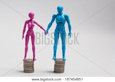 Male And Female Figurines Holding Hands And Standing On Top Of Equal Piles Of Coins. Income Equality