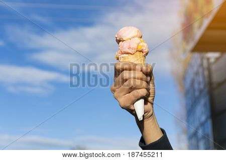 Hand holding ice cream with blue sky background