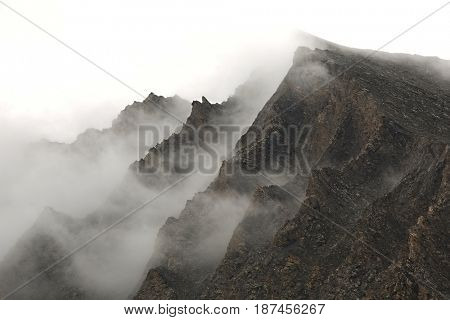 High mountains ridge in thick fog