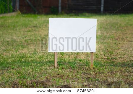 Empty signboard on a piece of ground