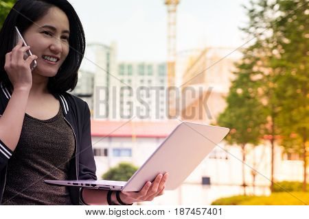 A Woman Is On Call And Holding Laptop Computer