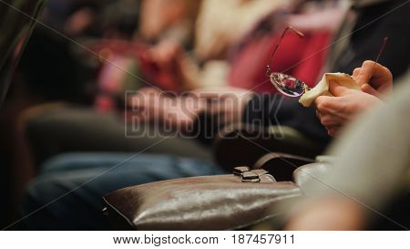 Woman sitting in a concert hall holds glasses and rubs