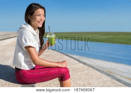 Healthy morning breakfast runner athlete drinking green smoothie juice drink cup before race for an active workout. Asian running woman happy looking at stadium blue tracks before cardio workout.