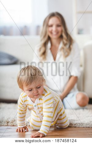 crawling baby boy on living room floor, mothe on second pland out of focus