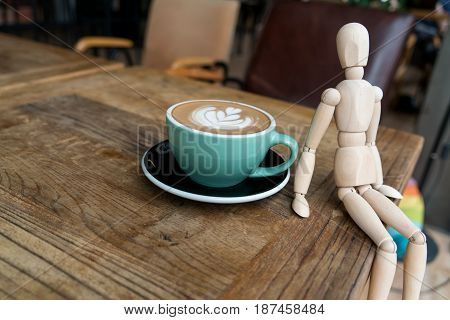Hot Mocha Coffe Or Capuchino In The Green Cup With A Wood Man Sitting On The Wooden Table