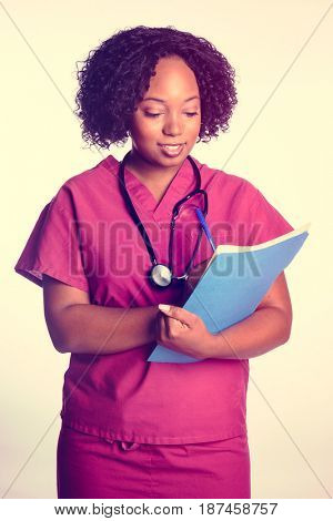 Woman nurse taking notes on chart