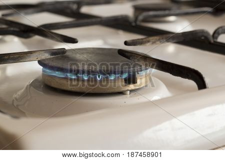 The gas burner burns with a small blue flame