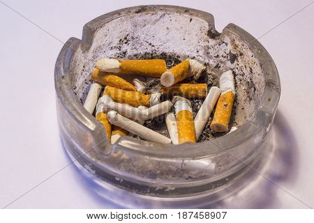 Cigarette stubs with filter are in a dirty ashtray with ash