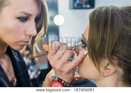 Make-up artist doing makeup to beautiful young girl in the studio. visagiste paints eyelids.