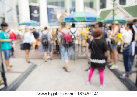 blurred background of people inside Erawan shrine at Ratchaprasong Junction in Bangkok Thailand.