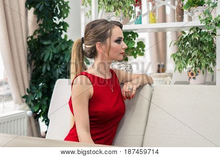 Businesswoman sitting on the sofa at the restaurant. Blonde lady in red. She is waiting for a meeting