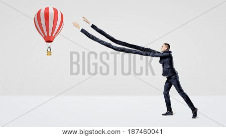 A businessman in side view trying to catch a large flying hot air balloon with his extra-long arms. Reach for dream. Travelling and exploration. Inhuman effort.