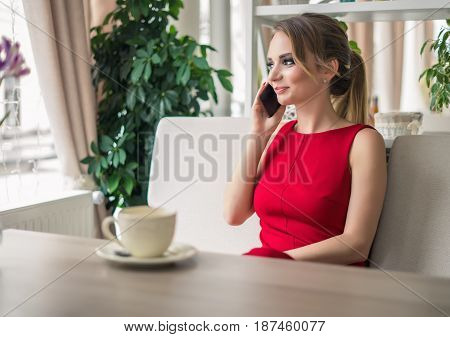 Businesswoman speaking on smartphone taking a coffee break. She is laughing. lady in red