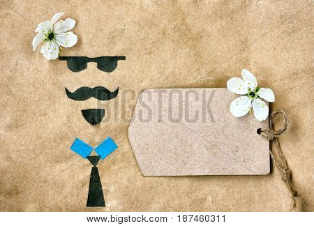 Father's day greeting card applique face with glasses mustache and beard paper tag with flower on crumpled kraft paper