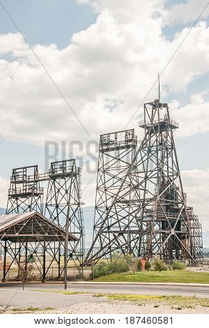 Mining headframes stand out against clouds and a blue sky