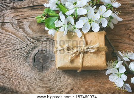 Gift box and a branch of flowering plum on a wooden table macro sunlight