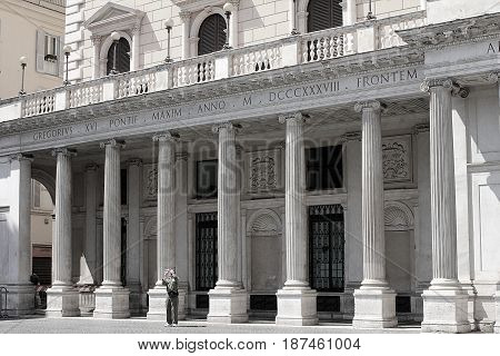 Rome, Italy, in black and white. Facade of Galleria Colonna, (since 2003 Galleria Alberto Sordi) in Piazza Colonna, May 5, 2012. A tourist is taking picture of Column of Marcus Aurelius in the center of  Piazza Colonna.