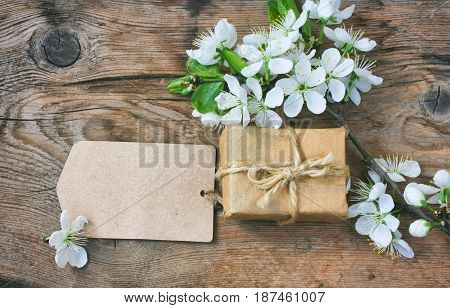 Gift box blank paper tag and branch of a flowering plum on a wooden table macro birthday