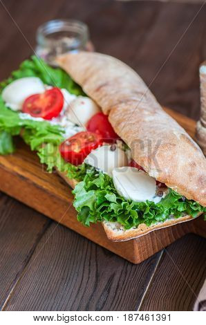 Сiabatta Sandwich With Cherry Tomatoes Mozzarella Lettuce Salad Leaf Sour Cream Sauce Served On Boar