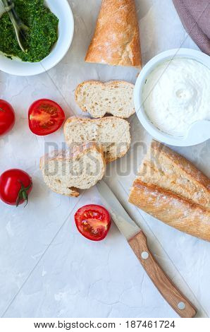 Set of ingredients for bruschettas with goat cheese pesto sauce and tomatoes and baguette on a white stone background. Top view and copy space.