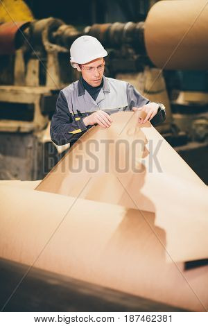 papper mill factory worker checking the quality of product