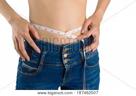 Woman on white in blue jeans tape measure her waist and hips with measuring tape isolated with white background.