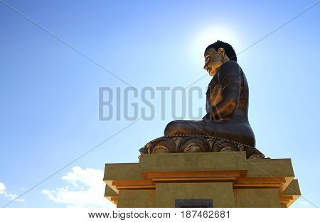 Buddha Dordenma statue on blue sky background with sun light Giant Buddha Thimphu Bhutan