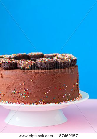Rich Chocolate Birthday Cake With Colorful Confetti And  Baked Chocolate Doughnuts Over Blue And Pin