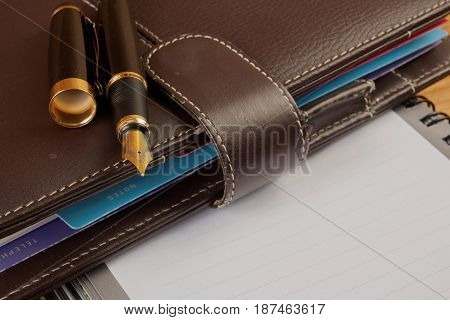 Fountain pen and notebook on wood table