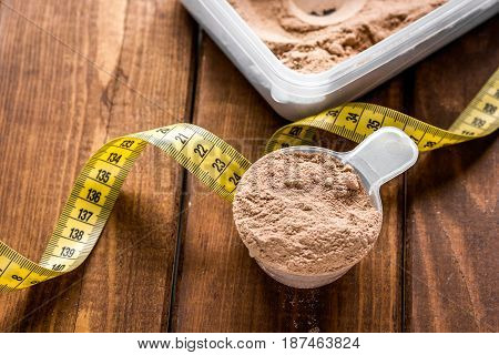 nutrition for workout with protein cocktail powder, measure tape on wooden table background close up