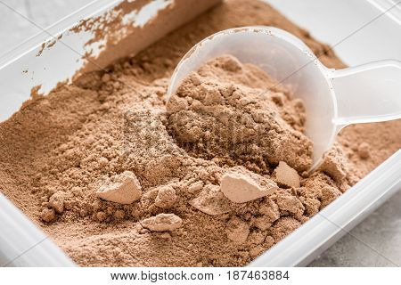 Whey protein powder for fitness nutrition to start training on stone background