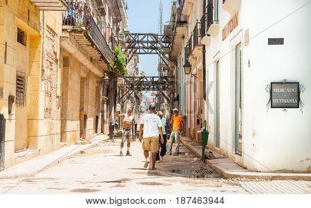 Havana, Cuba - June 30, 2012; Workmen in dilapidated buildings in street undergoing significant restoration of historic buildings as tourist walks through in Havana.