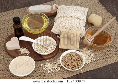Natural ingredients to heal skin disorders with oats, honey, almond oil, moisturizer, soap and essential oil on hessian over oak wood background. Treatment will help soothe psoriasis and eczema.