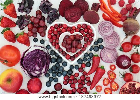 Purple and red health food with fruit and vegetables in heart shaped porcelain dishes and loose on distressed wood background. High in antioxidants, vitamins, anthocyanins and dietary fiber.
