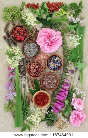 Natural herbal medicine selection with dried and fresh flowers and herbs on hemp paper background.