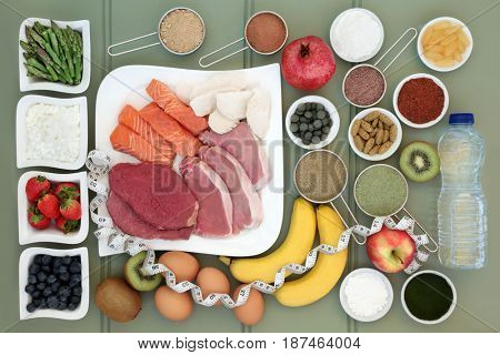 Body building healthy food collection of meat, fish, supplement powders,vitamin pills,fruit, dairy, bottled water and tape measure over slate background.