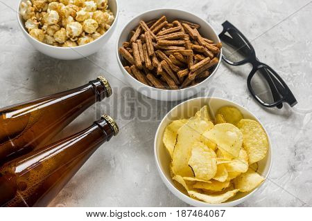 film whatching party with beer, crumbs, chips and pop corn on stone background