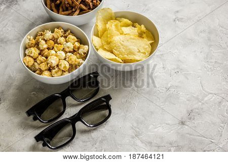 film whatching party with glasses, crumbs, chips and pop corn on stone background mockup