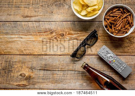 home party with TV watching, snacks, chips and bread crumbs and beer on wooden background top view mock up