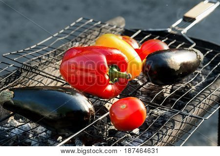 Close up grilled vegetables on the grid grill close up. Red and yellow pepper eggplant and tomato on the grid grill